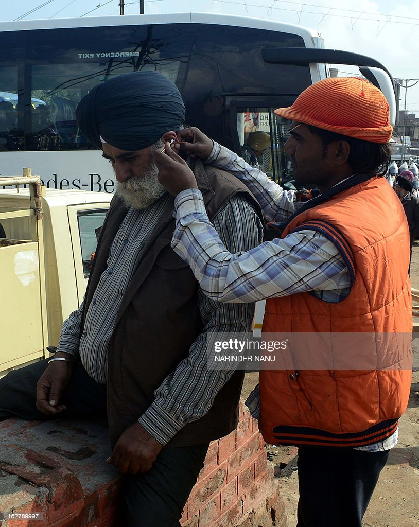 Indian ear-cleaner Sunil Kumar (R) tends to a customer on the road in Amritsar on February 27, 2013. Ear-cleaners, or Kaan Saaf Wallahs as they are locally known, are a common sight in Indian cities where customers pay to have wax and dirt scraped from inside their ears. AFP PHOTO/ NARINDER NANU