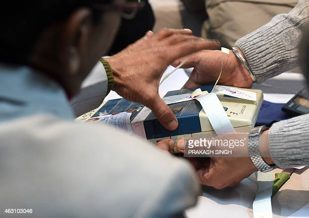 Indian election officials open a Electronic Voting Machine at a vote counting centre in New Delhi on February 10 2015 Counting of votes started for...