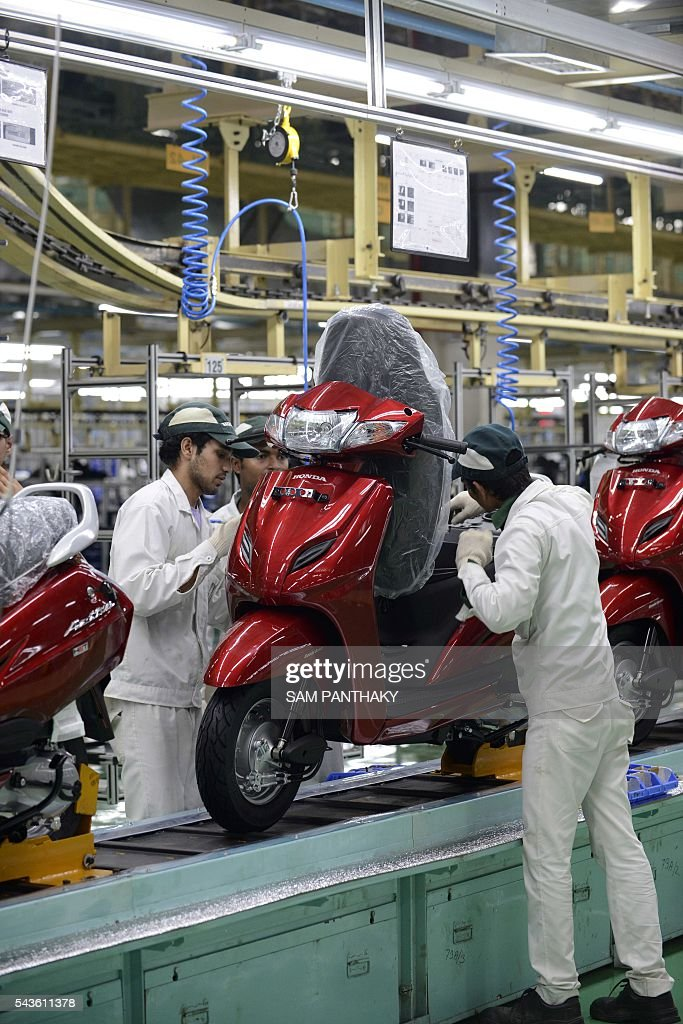 Indian employees check an Honda Activa scooter before it rolls down the second assembly line of Honda's fourth plant in India at Vithalapur, some 80 kms from Ahmedabad on June 29, 2016. The second assembly line was inaugurated June 29 by Keita Muramatsu, president and CEO of Honda Motorcycle and Scooter India (HMSI). Production expands by 0.6 million units to 1.2 million units annually at India's fourth plant at Vithalapur in Gujarat. / AFP / SAM