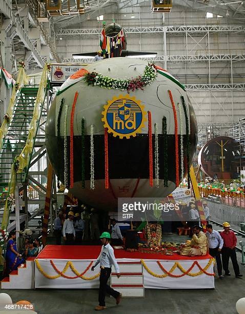 Indian employees of the Mazgaon ship building yard gather around the first Scorpene submarine before it is floated for sea trials in Mumbai on April...