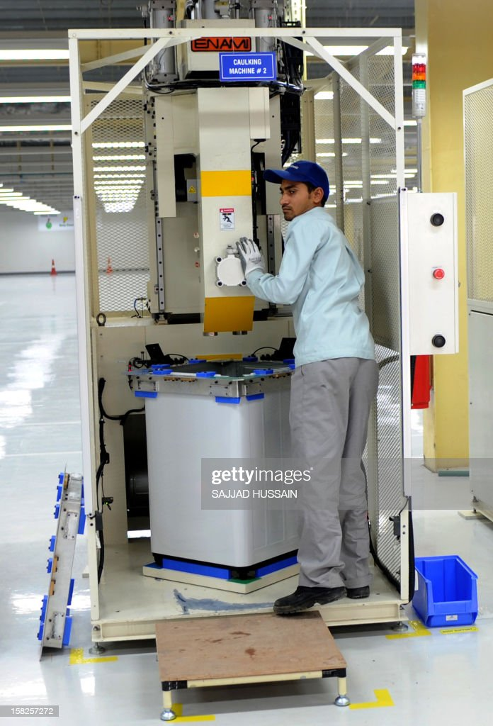 Indian employees work on a washing machine unit at the Panasonic 'eco ideas' factory at Jhajjar in Haryana on December 12, 2012. Panasonic India today announced the expansion of its presence in India with the opening of its first model 'eco ideas' factory. This is the company's latest initiative to showcase best practices in sustainable manufacturing and raise level of eco consciouness in the community through outreach activities.