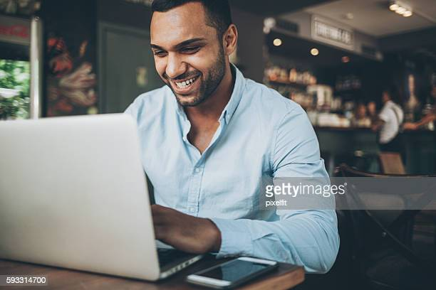 Indian ethnicity man working on laptop in cafe