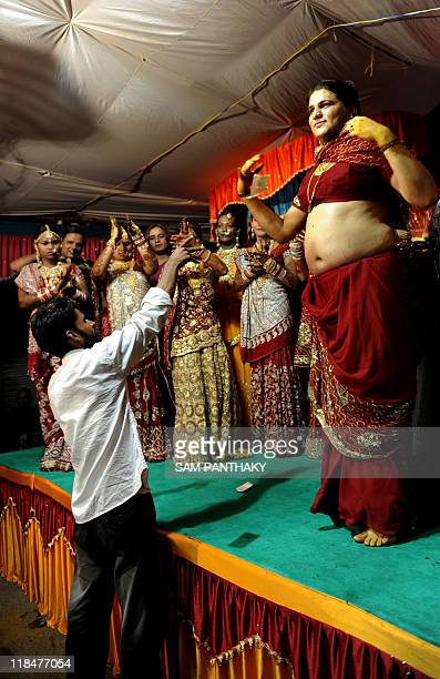 Indian eunuchs dance as a man showers banknotes towards them during their wedding reception in Ahmedabad on July 12 2009 In the presence of some one...