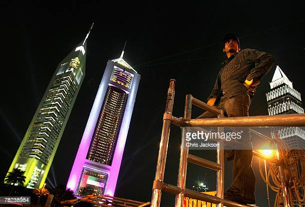 Indian expatriot workers construct an advertising hoarding late at night in front of the iconic Emirates Towers on December 3 2007 in Dubai United...