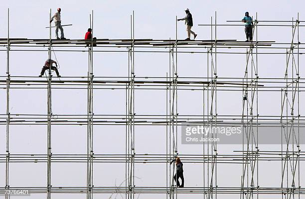 Indian expatriot workers set up a giant advertising hoarding next to the motorway in the desert on April 2 2007 in Dubai United Arab Emirates...