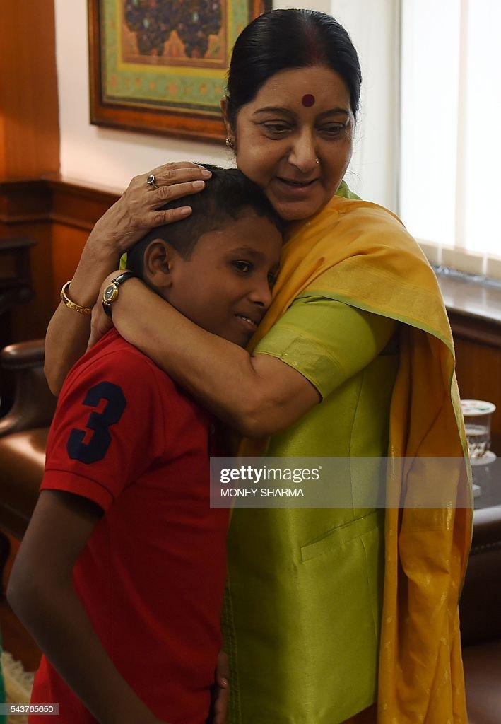 Indian External Affairs Minister, Sushma Swaraj (R) hugs 12 year-old boy, Sonu on meeting him and his parents at the Ministry of External Affairs in New Delhi on June 30, 2016. Sonu, a 12-year-old Indian boy who was kidnapped from New Delhi and taken to neigbouring Bangladesh six years ago, finally returned home on June 30 to be reunited with his parents. / AFP / MONEY