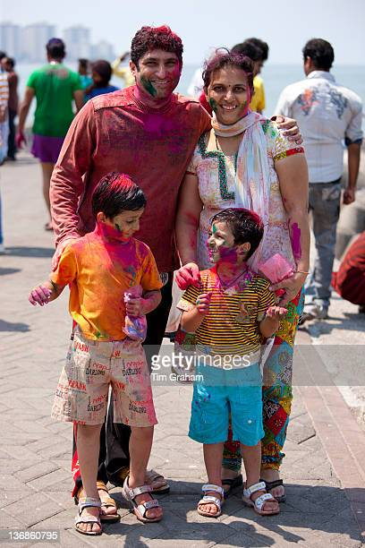 Indian family celebrating annual Hindu Holi festival of colours with powder paints at Nariman Point in Mumbai formerly Bombay India