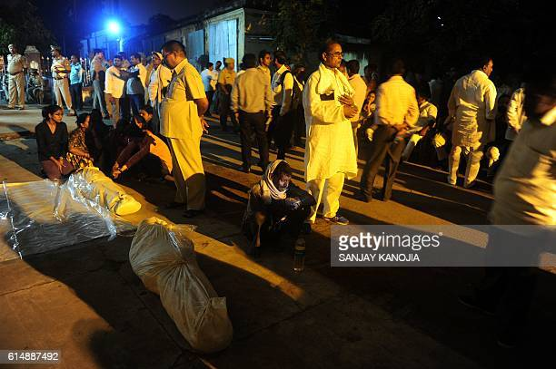 Indian family members sit near dead bodies outside the BHU morgue following a fatal stampede in Varanasi on October 15 2016 A stampede at a religious...