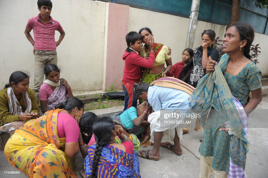 Indian family members weep after seeing the bodies of those killed in a wall collapse, as they sit outside the mortuary at Gandhi Hospital in Hyderabad on July 23, 2013. Six people were killed in their sleep in southern India when a mud wall collapsed on their makeshift tenements, rescue officials said. AFP PHOTO / Noah SEELAM