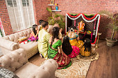 Indian  family performing Ganesh puja or Ganpati Puja in Ganesh Utsav, or holding ganesh idol over white background