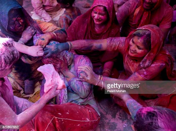 Indian family rub colour powers on each other at the Sri Banke Bihari temple as they celebrate Holi the festival of colour March 22 2008 in Vrindavan...