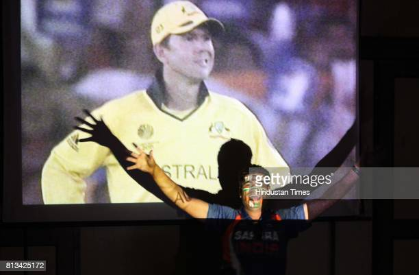 Indian fan celebrates as he watch live telecast of India and Australia match at a restaurant in Mumbai on Thursday