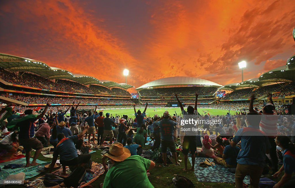 Indian fans in the crowd celebrate as a Pakistan wicket falls as the sun sets during the 2015 ICC Cricket World Cup match between India and Pakistan...