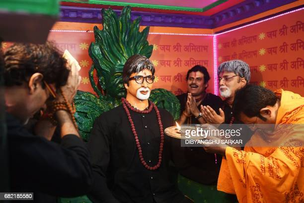 Indian fans of Bollywood actor Amitabh Bachchan perform a 'religious prayer' in front of a newly inagurated lifesized statue of the actor inside the...