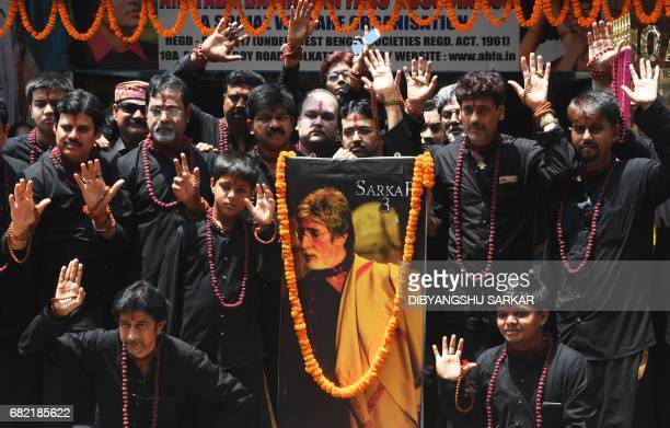 Indian fans of Bollywood actor Amitabh Bachchan pose with a poster featuring his image prior to the inauguration of a lifesized statue of the...