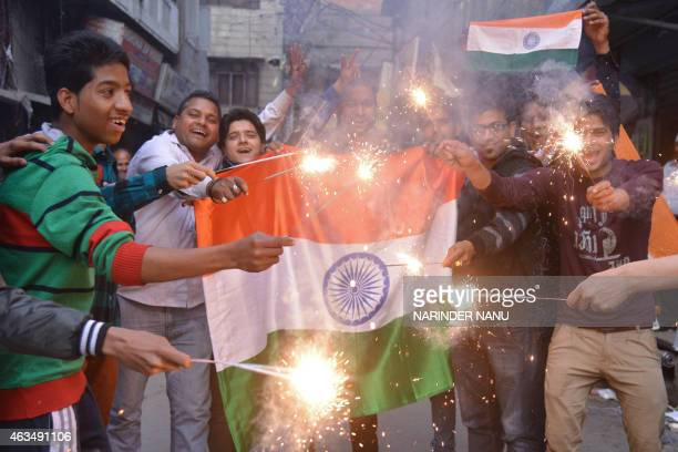 Indian fans pose with their national flags and hold sparklers as they celebrate after India won the 2015 Cricket World Cup's cricket match against...
