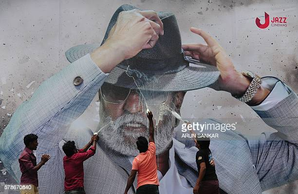 Indian fans spray milk on a poster of Bollywood star Rajinikanth outside a cinema on the first day of release of his new Tamillanguage film 'Kabali'...