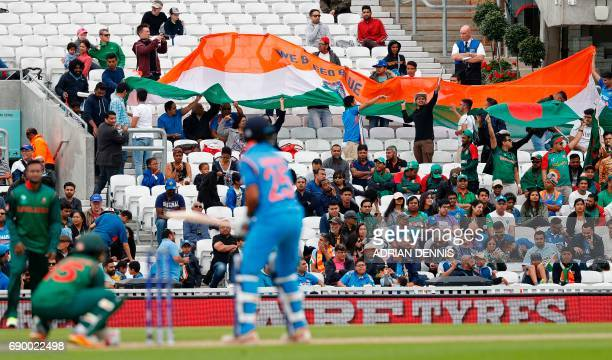 Indian fans unfurl a giant flag as India's Shikhar Dhawan prepares to play a shot during the ICC Champions Trophy Warmup cricket match between India...