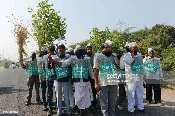 Indian farmers affected by the Gujarat Government's Special Investment Region and representing Khedut Samaj participate in a peaceful march holding...