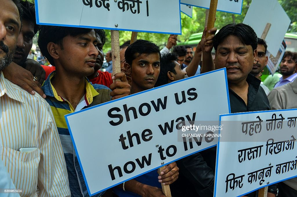 Indian farmers and micro-retailers hold banners and placards as they protest in New Delhi on May 31, 2016, against proposed reforms to the packaging of tobacco products on World No Tobacco Day. Members of Federation of All India Farmers Associations(FAIFA), representing the interest of thousands of tobacco growers along with members of Akhil Bhartiya Pan Vikreta Sanghathan(ABPVS), which presents the collective voice of the interests of traders selling tobacco products across India, took part in the protest against the repackaging campaign which they allege is aimed at destroying the local Indian tobacco industry. / AFP / CHANDAN