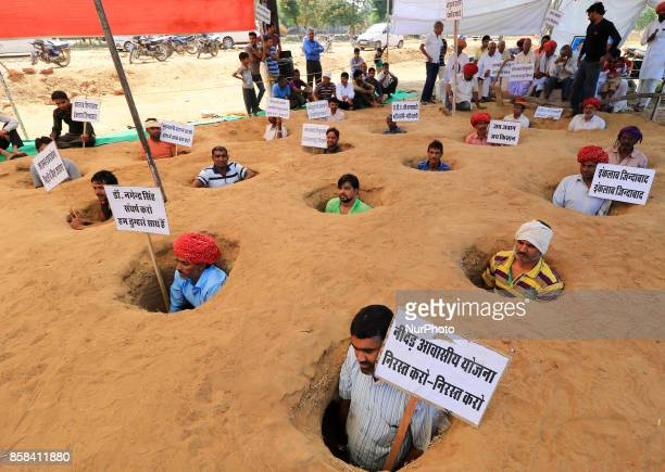 Indian farmers bury themselves in pits and hold the placards in Hindi reads Chief minister down down and free our land and Hail the Soldier Hail the...