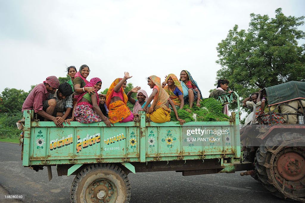 Indian farmers gesture from a tractor trailer as they head to the fields to plant rice paddy near Narimanpura village, some 30 kms from Ahmedabad, on July 13, 2012. Annual monsoon rains, crucial to India's economy, covered the country on July 11 but remained 23 percent below average, sparking fears of their impact on two cereal-producing states. The pounding rains that sweep across the continent from June to September are dubbed the 'economic lifeline' of India, which is one of the world's leading producers of rice, sugar, wheat and cotton. AFP PHOTO / Sam PANTHAKY