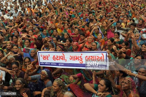 Indian farmers hold up a Gujarati language banner which reads 'remove the Special Investment Region save villages' during a rally in Gandhinagar...