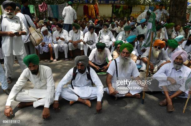 Indian farmers of the Bhartiya Kisan Union listen to their leader's speech during a protest against Prime Minister Narendra Modi and the Madhaya...