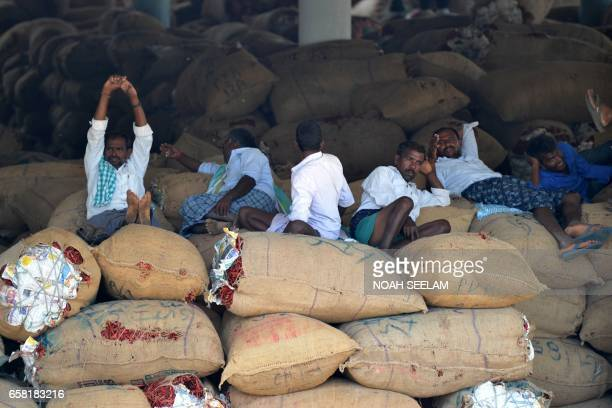 Indian farmers rest on sacks of dried red chillies bags as they wait for traders at a wholesale market in Hyderabad on March 27 2017 Despite a bumper...