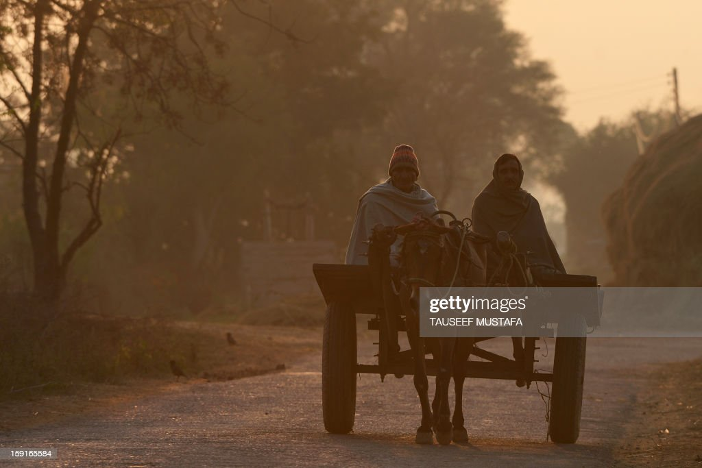 Indian farmers ride a horse cart as they return after a day's work near the India-Pakistan border in Abdulian, 38 kms southwest of Jammu, on January 9, 2013. India delivered a dressing-down to Islamabad's envoy to Delhi as it accused Pakistan's army of beheading one of two soldiers killed in Kashmir, but both sides warned against inflaming tensions. AFP PHOTO/Tauseef MUSTAFA