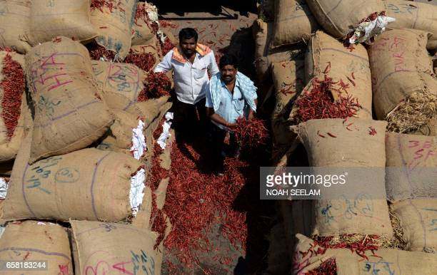 Indian farmers Yadaiah and Achaiah show their crop of dried red chillies at a wholesale market in Hyderabad on March 27 2017 Despite a bumper harvest...