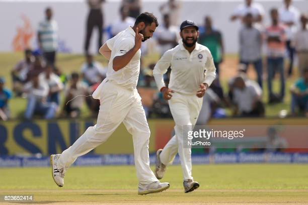 Indian fast bowler Mohammed Shami celebrates after taking a wicket as his team mate Cheteshwar Pujara joins in during the 2nd Day's play in the 1st...