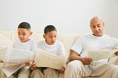 Indian father and sons reading newspaper