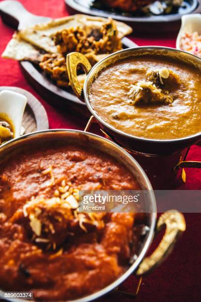 Indian feast with butter chicken, chicken tandoori, lamb curry, vegetable curry, samosas, pakoras, bhajis, naan bread and basmati rice on a table. North Indian food