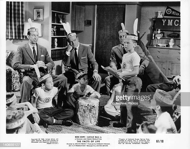Indian feather wearing Bob Hope two men and children wathc child speaking before the group in a scene from the film 'The Facts Of Life' 1960