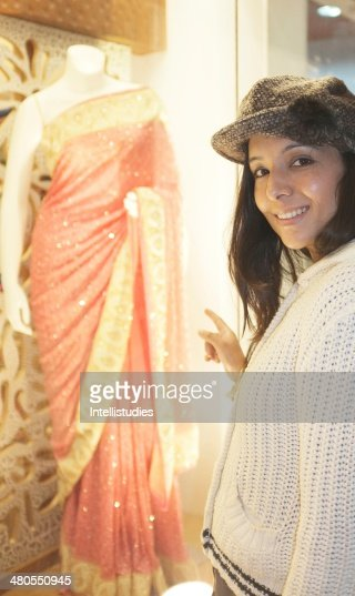 Indian female excitedly pointing towards a showroom. : Stock Photo