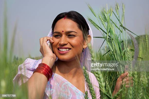 Indian female farm worker looking away while talking on mobile phone