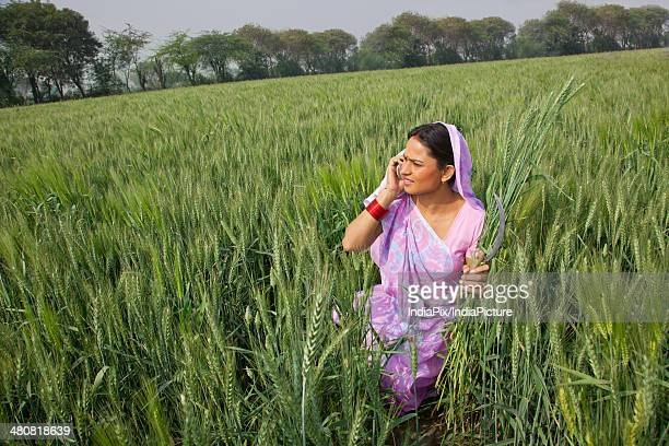 Indian female farmer using cell phone while working in field