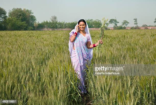 Indian female farmer using mobile phone while walking in farm