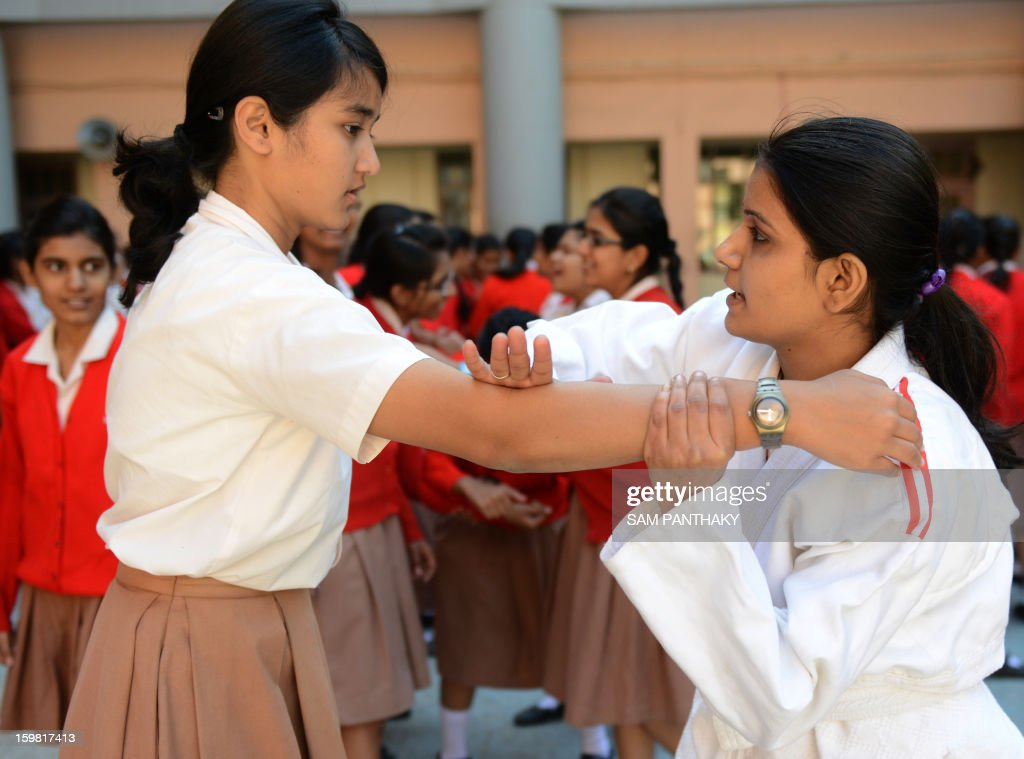 Indian female high school students try out basic Judo skills as they participate in a camp for self defense in Ahmedabad on January 21, 2013. Increasing crime against women and girls with the recent Delhi gang-rape and many similar crimes in Gujarat state are compelling women and girls to protect themselves with basic defence skills like judo and karate. AFP PHOTO / Sam PANTHAKY