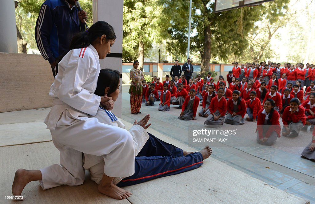 Indian female high school students watch an exhibition of basic Judo skills as they participate in a camp for self defense in Ahmedabad on January 21, 2013. Increasing crime against women and girls with the recent Delhi gang-rape and many similar crimes in Gujarat state are compelling women and girls to protect themselves with basic defence skills like judo and karate. AFP PHOTO / Sam PANTHAKY