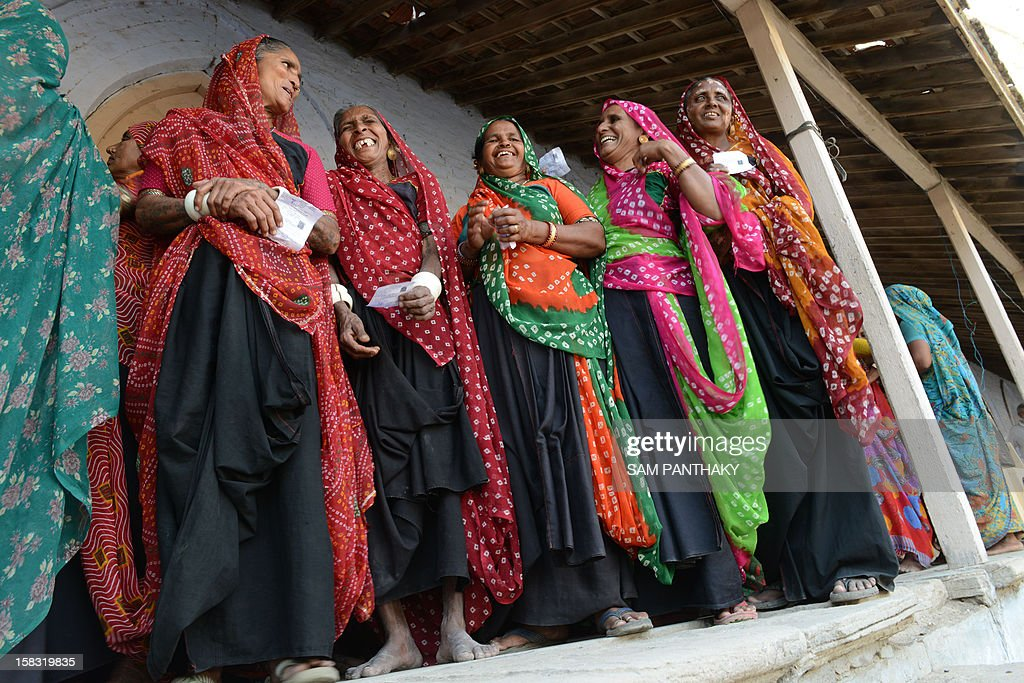 Indian female voters wait in line to cast their ballot in the state assembly elections at Sanand town, some 30 kms from Ahmedabad on December 13, 2012. The first phase of voting in state assembly elections in the western Indian state of Gujarat started with the next phase on December 17, 2012. AFP PHOTO/ Sam PANTHAKY