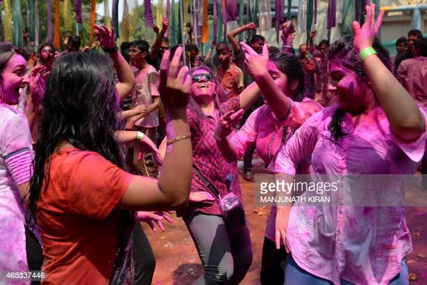 Indian festive revellers are smeared with coloured powders as they dance during Holi celebrations in Bangalore on March 6 2015 Holi the festival of...