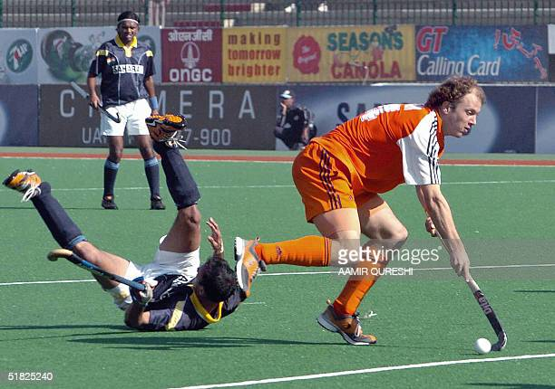 Indian field hockey player Vivek Gupta lies on the ground after colliding with Netherlands player Teun de Nooijer during the SixNations Champions...