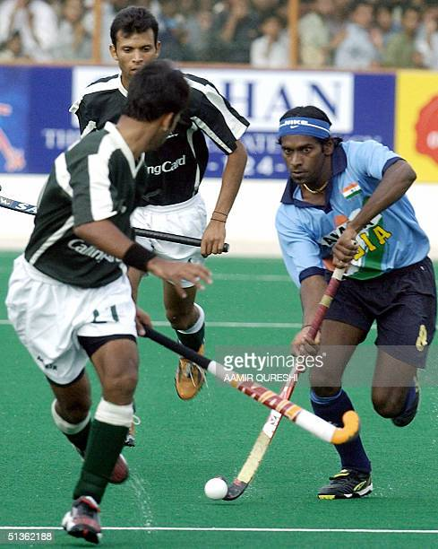 Indian field hockey team player VS Vinay dribbles past Pakistani players during the second field hockey match between Pakistan and India in the Ayub...