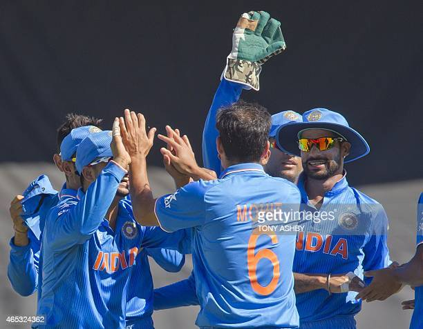 Indian fielder Mohit Sharma celebrates with teammates after returning a ball to cause the run out of West Indies batsman Marlon Samuels during the...