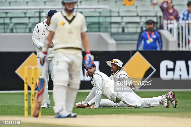 Indian fieldsmen Ravi Ashwin and Shikhar Dhawan react after dropping Australian batsman Chris Rogers during the fourth day of the third cricket Test...