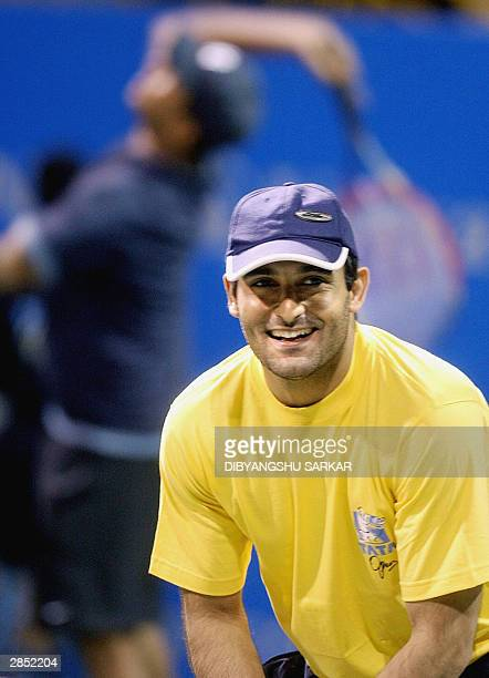 Indian film actor Akshaye Khanna smiles as his partner Indian tennis player Mahesh Bhupati serves during a charity match at the Tata Open Tennis...