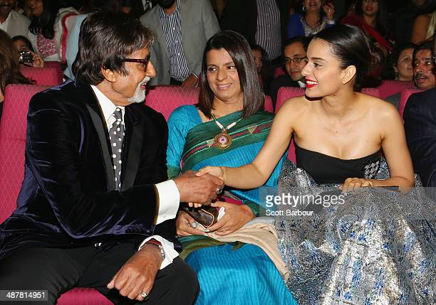 Indian film actor Amitabh Bachchan greets Indian actress Kangana Ranaut as her sister Rangoli Ranaut looks on during the Indian Film Festival of...