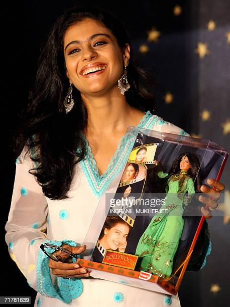 Indian film actress Kajol holds a replica doll of herself and Hrithik Roshan as she speaks at a function to launch replica dolls of Bollywood stars...
